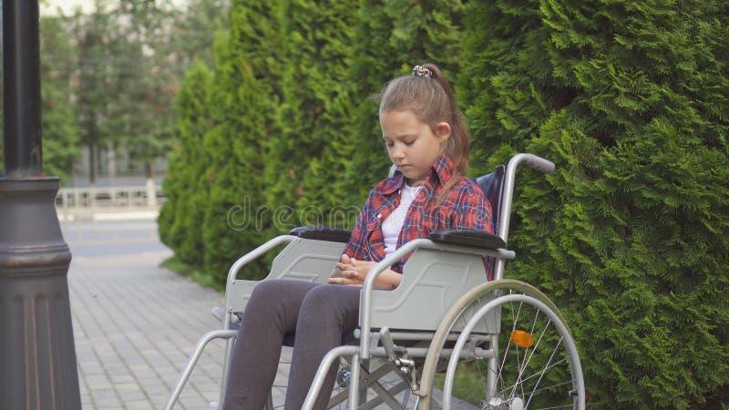 Dziewczyna jest niepełnosprawnym osobą w wózku inwalidzkim jest smutny jeden zdjęcia royalty free