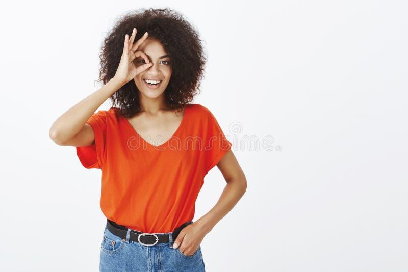 Dziewczyna jest pewna w jej zdolność Atrakcyjna pozytywna kobieta z afro ostrzyżeniem trzyma rękę w kieszeni i pokazuje ok, lub fotografia royalty free
