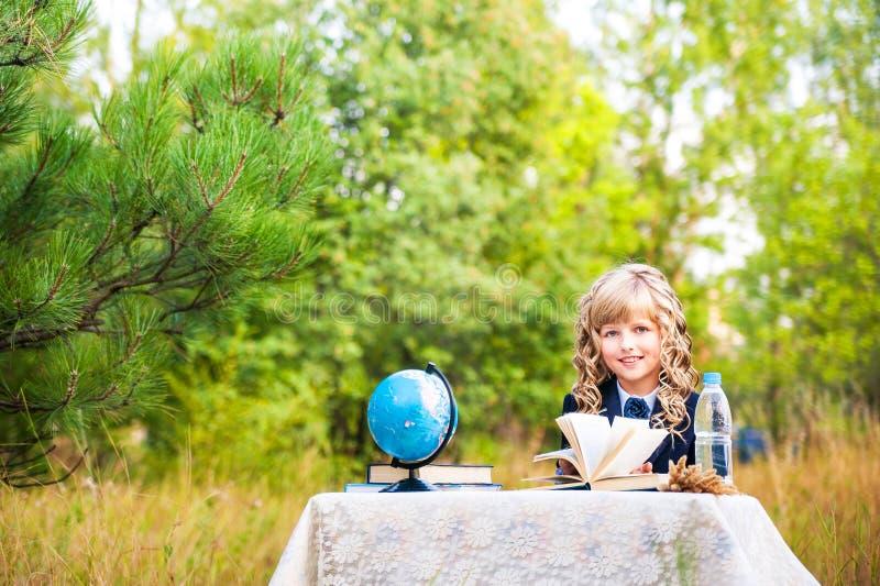 Dziewczyna jest pierwszy równiarki obsiadaniem przy mieniem i stołem otwarta książka w ona ręki Uczennica w błękitnym kostiumu kę obraz royalty free