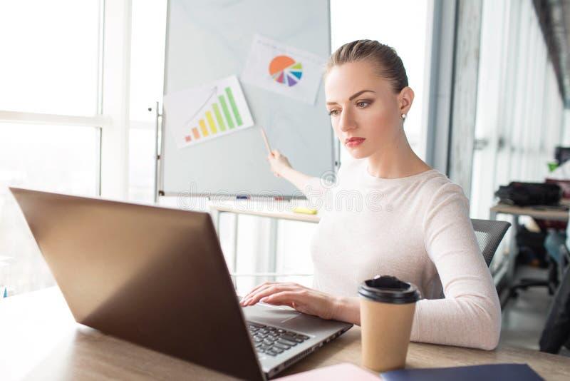 Dziewczyna jest przyglądająca laptop i demonstrować diagramy na biurku Pracuje teraz Młoda kobieta patrzeje bardzo fotografia stock