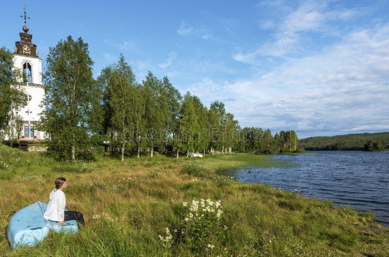 Dziewczyna jest siedząca wewnątrz na wracający korowatym i patrzeje Storan-Osterdalalven jezioro jest przy dobrem kośćiół protest zdjęcia royalty free