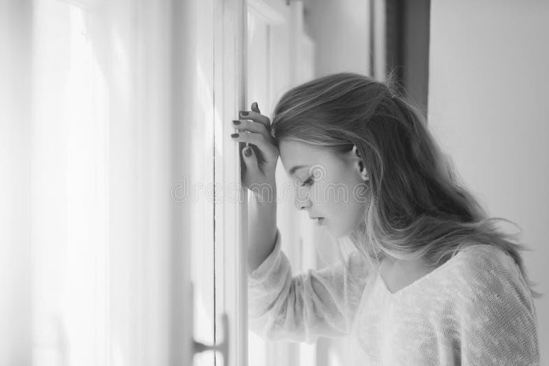 Dziewczyna jest smutna przy okno Ładna dziewczyny pozycja przy okno zdjęcia stock