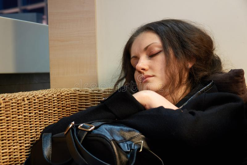 Dziewczyna jest sypialnym obsiadaniem w łozinowym drewnianym krześle podczas gdy czekający odjazd fotografia stock