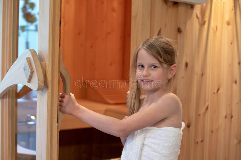 Dziewczyna jest uśmiechnięta i otwiera drzwi Fiński sauna obraz royalty free