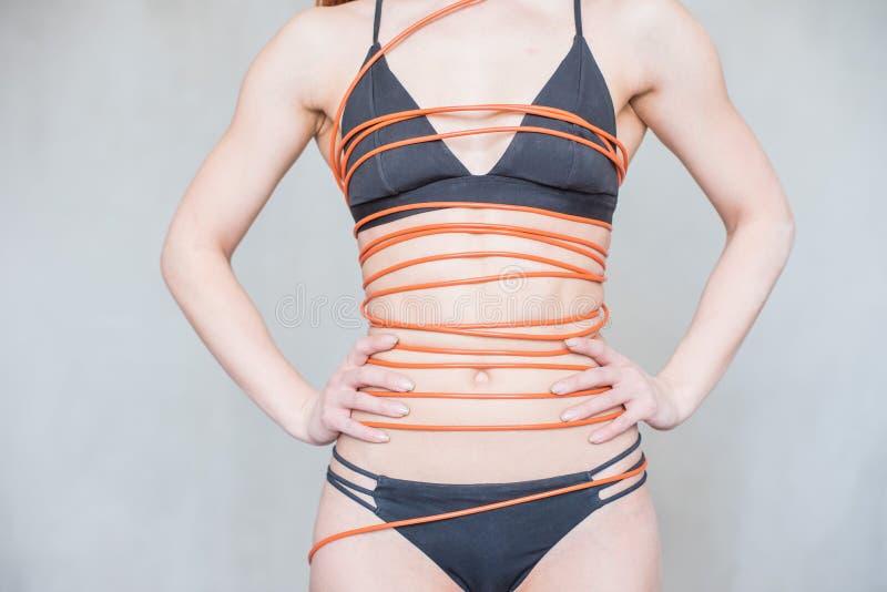 Dziewczyna jest ubranym czarnego swimsuit z czerwonym włosy, zawijającego w gęstym, długim pomarańczowym elektrycznym kablu, obrazy royalty free