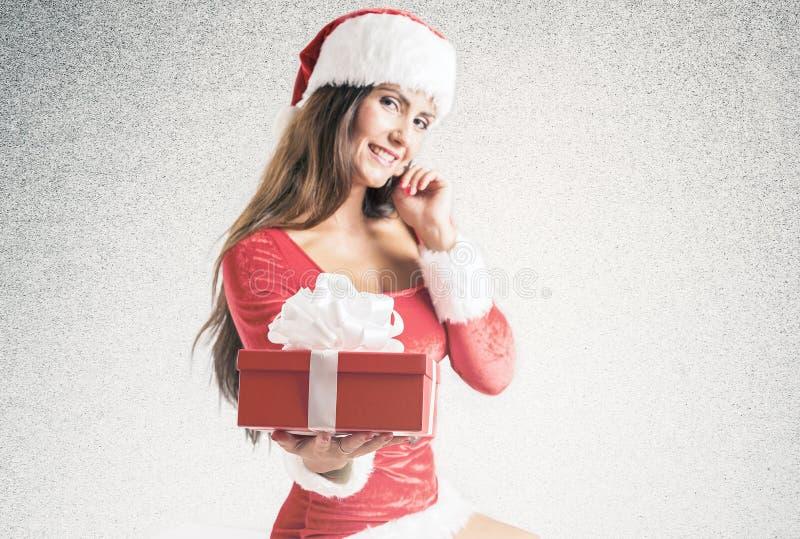 Dziewczyna jest ubranym Santa Claus odziewa z boże narodzenie prezentem zdjęcia stock