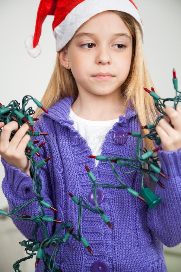 Dziewczyna Jest ubranym Santa Kapeluszowych Patrzeje Czarodziejskich światła obraz royalty free