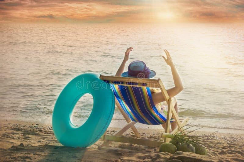 Dziewczyna jest ubranym szerokiego ronda słońca kapeluszowego obsiadanie na pokładu krześle plenerowym plażą z kokosowy i błękitn obraz stock