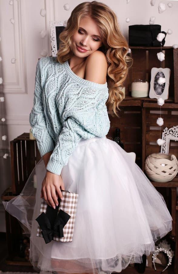 Dziewczyna jest ubranym trykotowego kardigan i fatin spódnicę pozuje obok choinki, zdjęcie royalty free