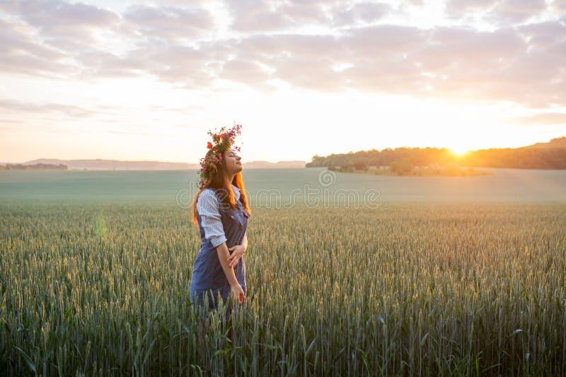 Dziewczyna jest ubranym wianek przy świtem w polu obrazy stock