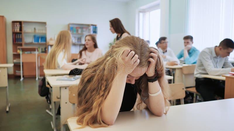 Dziewczyna jest uczennicy płaczem w klasie i jej kolega z klasy pocieszają ona zdjęcie stock
