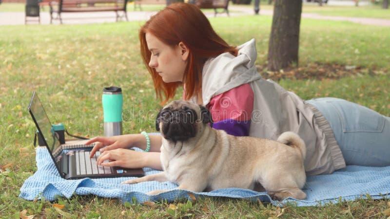 Dziewczyna kłaść i pisać na maszynie na laptopie na gazonie z jej mopsem wokoło zdjęcia stock
