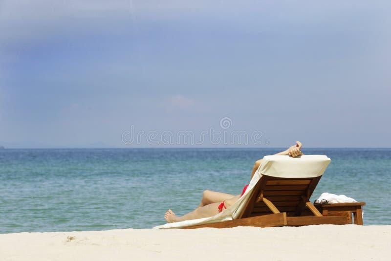 Dziewczyna kłama puszek na sunbed w pustej i cichej plaży przy Cholburi, Tajlandia obrazy royalty free