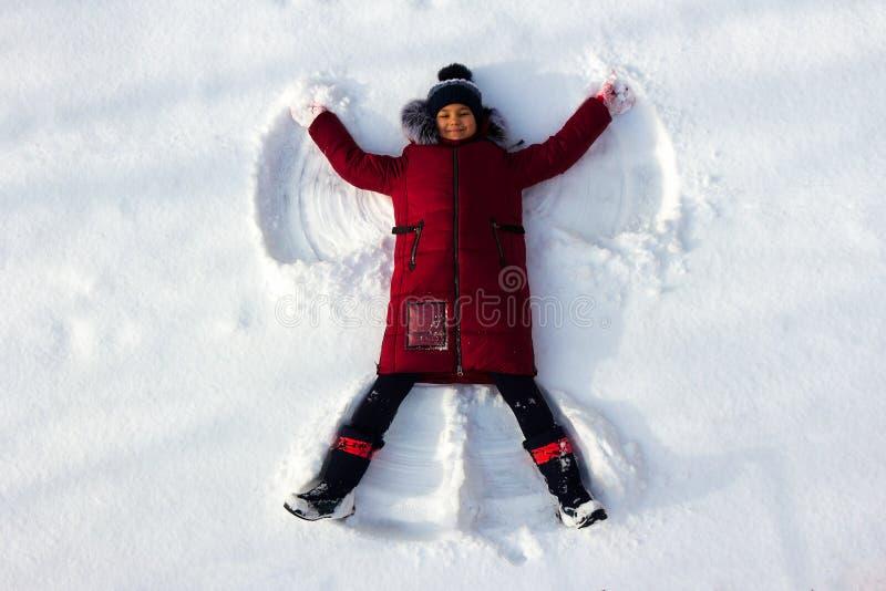 Dziewczyna kłama w śniegu i robi śnieżnemu aniołowi zdjęcia stock