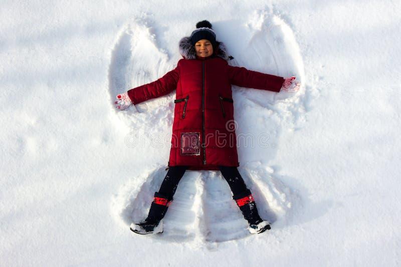Dziewczyna kłama w śniegu i robi śnieżnemu aniołowi fotografia royalty free