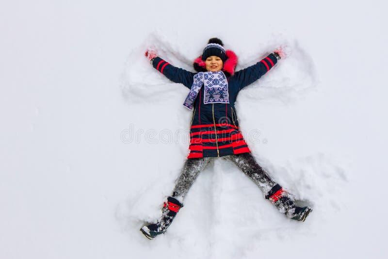 Dziewczyna kłama w śniegu i robi śnieżnemu aniołowi obrazy royalty free