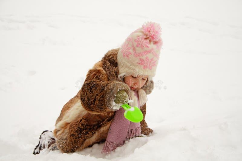 dziewczyna kopiący śnieg zdjęcia stock