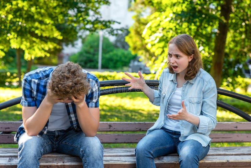Dziewczyna krzyczy przy młodym człowiekiem Lato w parku na ławce Facet jest płaczący i smutny, spinający jego głowę w jego ręki obraz stock