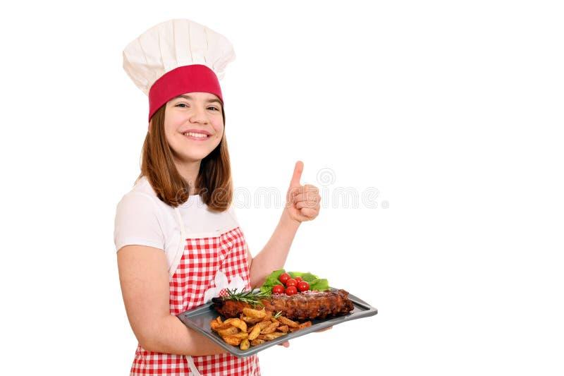 Dziewczyna kucharka z żeberkami wieprzowymi na talerzu i kciuk w górę obraz stock