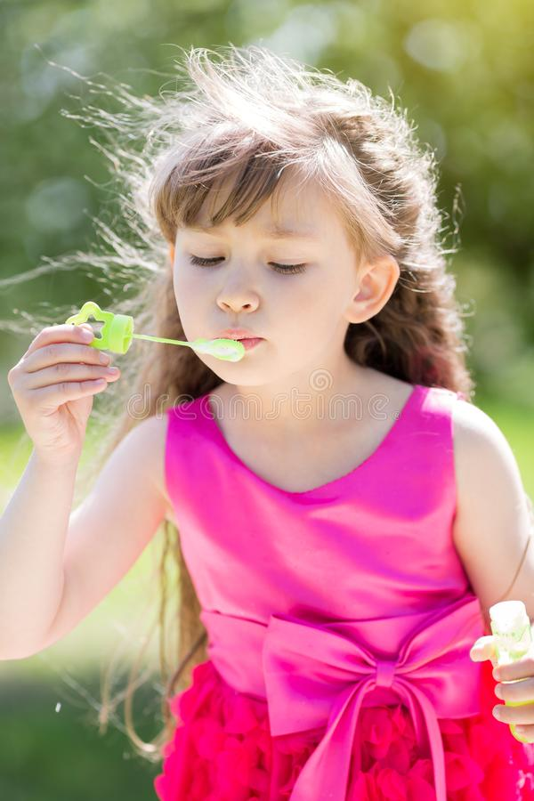 Dziewczyna 5 lat pozwala out mydlanych bąble obraz stock