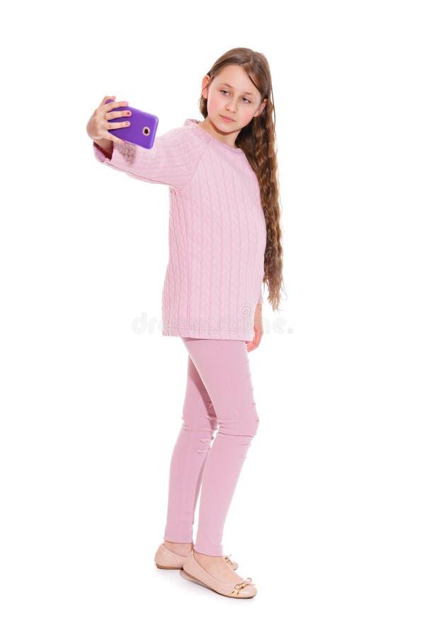 Dziewczyna 10-11 lat w różowym kostiumu bierze selfie od smartphone Odosobnienie na bielu obraz stock