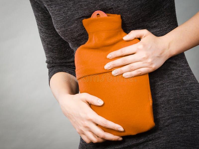 Dziewczyna ma żołądek obolałość, trzyma gorącej wody butelkę fotografia stock
