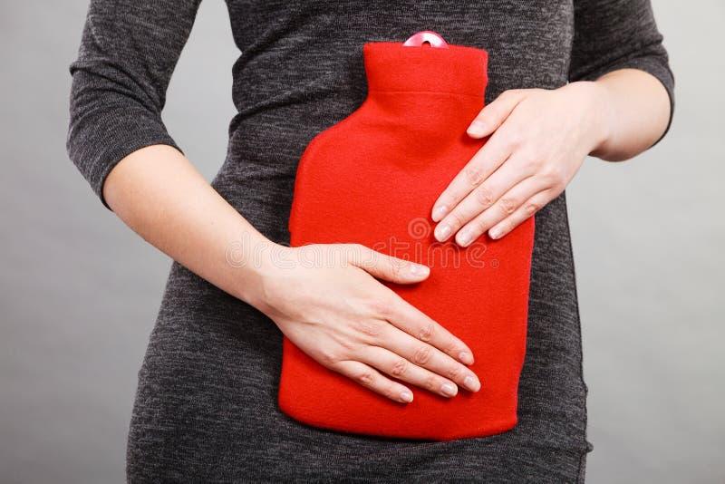 Dziewczyna ma żołądek obolałość, trzyma gorącej wody butelkę obraz stock