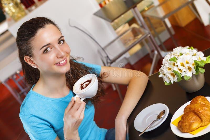 Dziewczyna ma kawową przerwę z sercem kształtował cappuccino fotografia royalty free