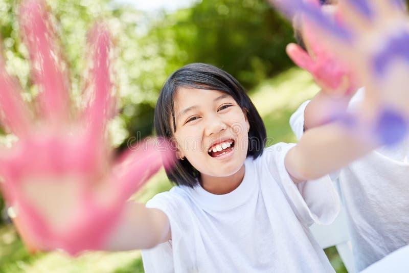Dziewczyna ma zabawę podczas gdy malujący z palcową farbą obrazy royalty free