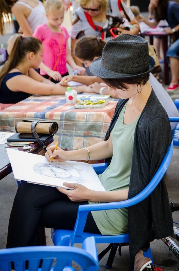 Dziewczyna malarz rysuje ołówek portret kobieta na miasta hol zdjęcie royalty free