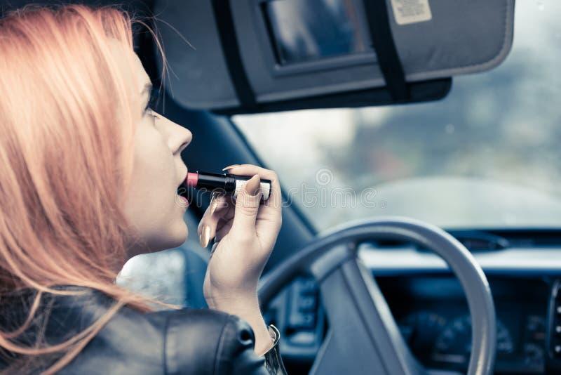 Dziewczyna maluje jej warg robić uzupełniał podczas gdy jadący samochód fotografia royalty free