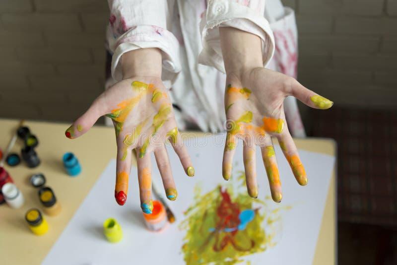 Dziewczyna maluje obrazek z kolorami używać jej swój ręki zdjęcia stock