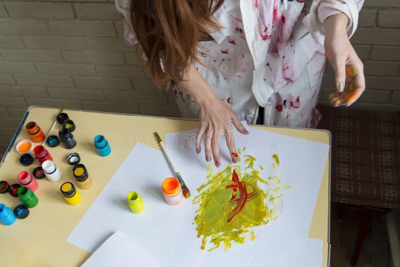 Dziewczyna maluje obrazek z kolorami używać jej swój ręki zdjęcie stock