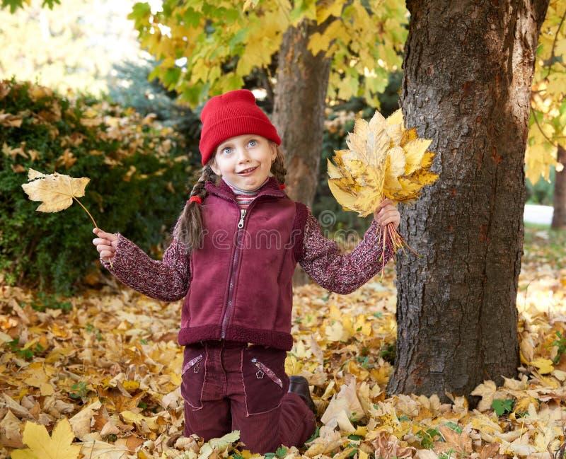 Dziewczyna mieć zabawę robi twarzom w jesień lesie, kolorów żółtych liściach i drzewach, na tle obraz stock