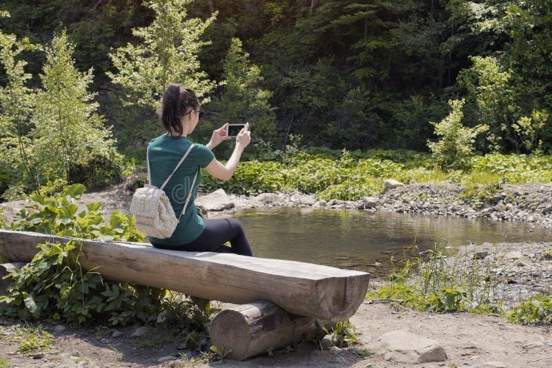 Dziewczyna na brzeg rzeki robi fotografii na smartphone widok z powrotem obrazy stock