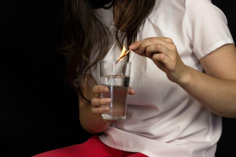 Dziewczyna na czarnym tle trzyma szkło woda i gasi dopasowanie, ból i palenie w żołądku płonących, zgaga zdjęcia stock