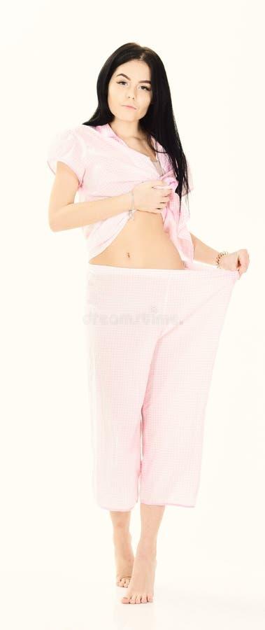 Dziewczyna na diecie gubił udział ciężar, odizolowywającego na białym tle Dziewczyna na zadumanych twarzy przedstawień dużym rozm zdjęcia stock
