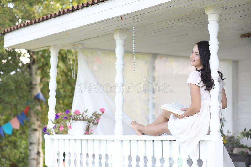 Dziewczyna na drewnianym ganeczku blisko domu obraz stock