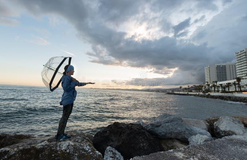 Dziewczyna na plaży blisko skał z parasolem na chmurnym dniu zdjęcie stock