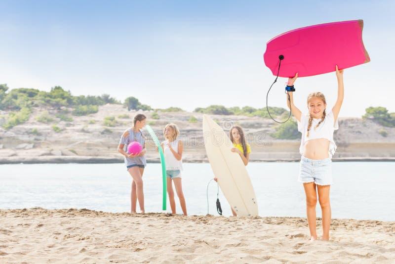 Dziewczyna na plaży z ciało deską i jej belzebubami fotografia stock