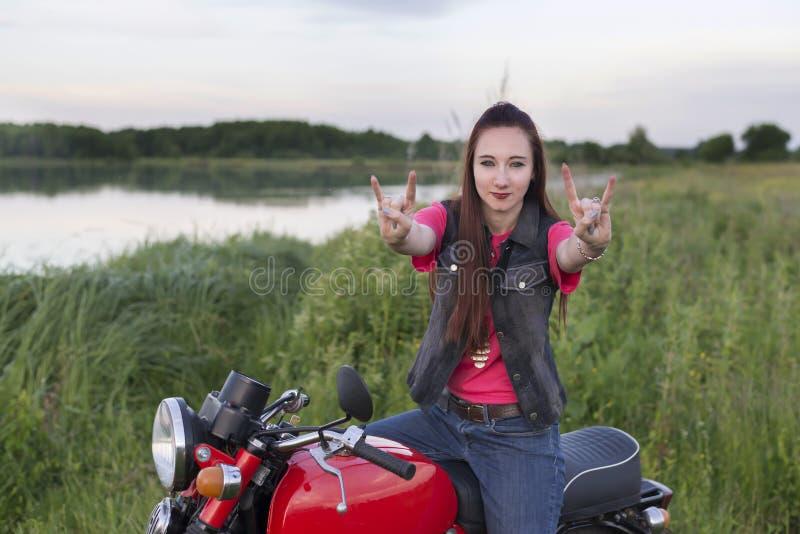 Dziewczyna na rocznika motocyklu pokazuje koźliego znaka outdoors obraz stock