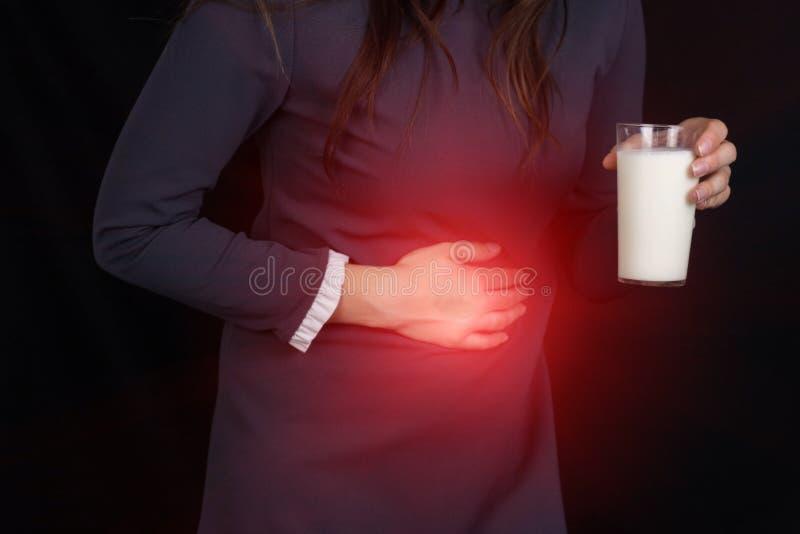 Dziewczyna na tła czarnych chwytach dalej jej żołądek, chwytach w ona i ręka szkło mleko, zgaga, brzuszny ból, Ups fotografia stock