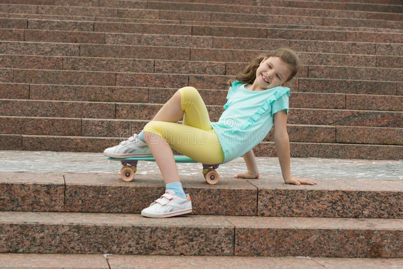 Dziewczyna, na tle kamienny schody, siedzi na sporty wsiada i uśmiechy obrazy royalty free