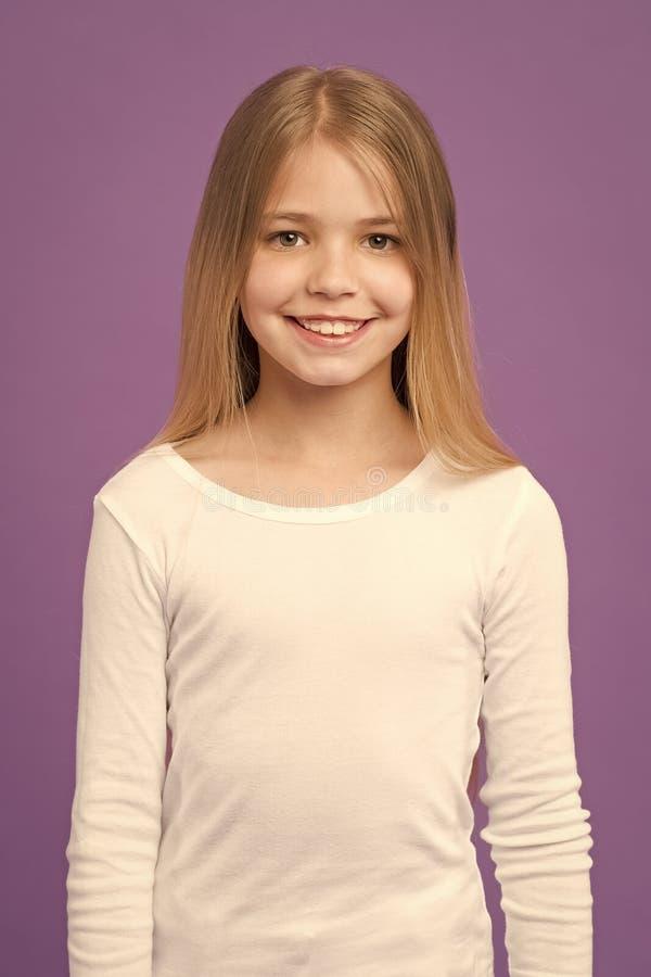 Dziewczyna na uśmiechniętej twarzy z długie włosy jest ubranym białą koszula, fiołkowy tło Dzieciak dziewczyna z długie włosy spo zdjęcie royalty free