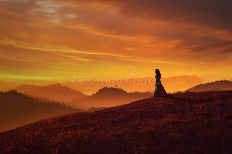Dziewczyna na wzgórzu przy zmierzchem obraz stock