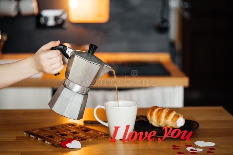 Dziewczyna nalewa gorącą kawę w kubku z słowami My KOCHA CIEBIE od czerwień papieru na stole z tortem, przeciw tłu zdjęcie stock