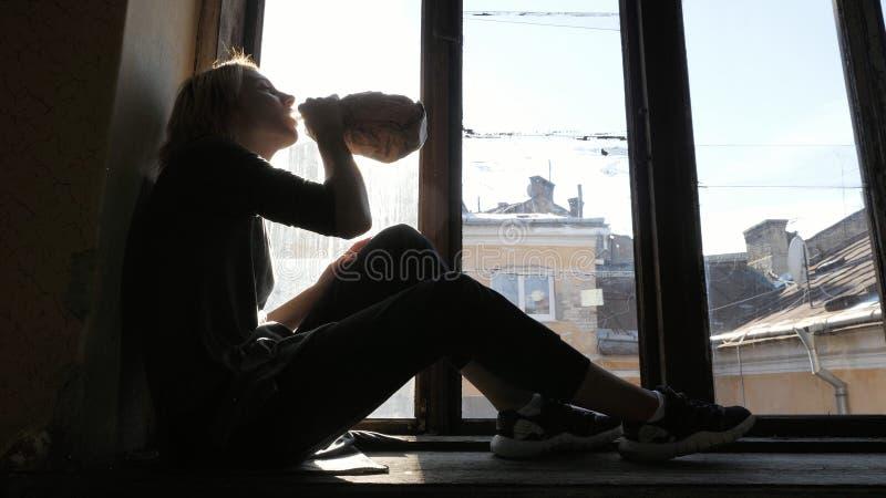 Dziewczyna napoju alkohol, siedzi dalej na windowsill Zakończenie zdjęcia stock