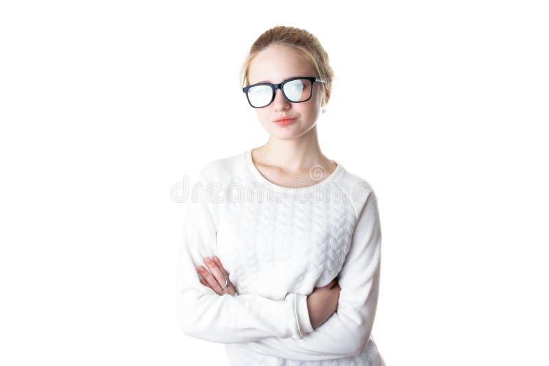 Dziewczyna nastolatek w szkłach i białym pulowerze, krzyżującym on ręki i uśmiechy pojedynczy białe tło obrazy royalty free