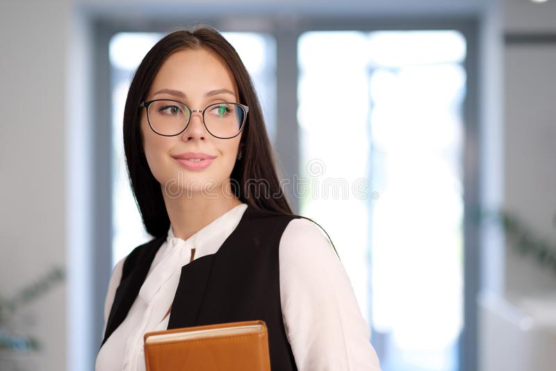 Dziewczyna nauczyciel w biurze lub uczeń Szkła i kostium, w rękach notatnik obraz royalty free