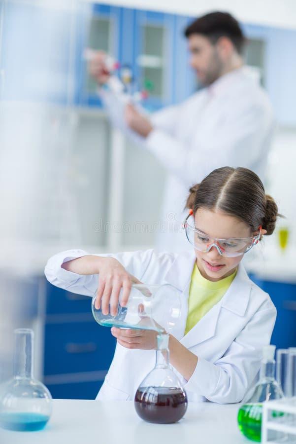 Dziewczyna naukowiec w ochronnych gogle robi eksperymentowi w chemicznym lab zdjęcia royalty free